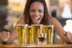 Mujer joven que mira fijamente emocionado un redondo de cervezas Fotos de archivo
