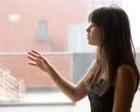 Mujer joven que mira fijamente hacia fuera ventana grande Imágenes de archivo libres de regalías