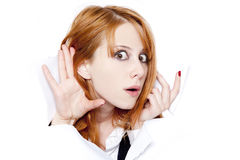 Mujer joven que mira furtivamente a través del agujero en el papel Imagen de archivo