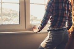 Mujer joven que mira hacia fuera la ventana Fotografía de archivo libre de regalías