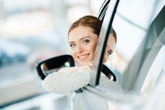 Mujer joven que mira hacia fuera la ventana del nuevo coche Fotos de archivo libres de regalías