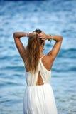 Mujer joven que mira la agua de mar en las vacaciones de verano que toman la cola de caballo en su pelo que disfruta de las vacac Imagen de archivo