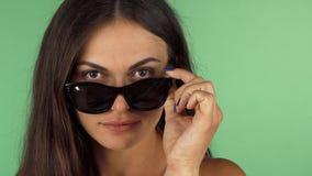 Mujer joven que mira a la cámara sobre sus gafas de sol almacen de video