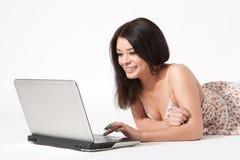 Mujer joven que mira la computadora portátil Foto de archivo