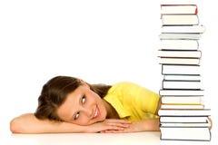 Mujer joven que mira la pila de libros Fotos de archivo libres de regalías