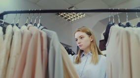 Mujer joven que mira la ropa, colgando en suspensiones almacen de metraje de vídeo