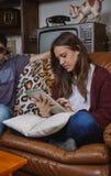 Mujer joven que mira la tableta electrónica que se sienta encendido Foto de archivo libre de regalías