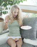 Mujer joven que mira la torta caida en las piernas en casa Fotografía de archivo libre de regalías