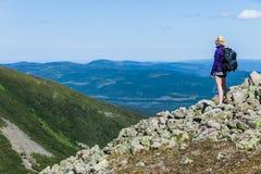 Mujer joven que mira la visión desde arriba de la colina fotografía de archivo
