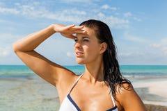 Mujer joven que mira lejos en la playa Imágenes de archivo libres de regalías