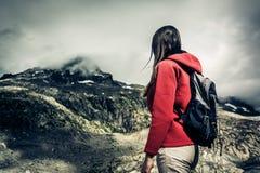 Mujer joven que mira para arriba al pico del ` s de la montaña Imagenes de archivo