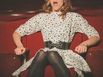 Mujer joven que mira película asustadiza Imagenes de archivo