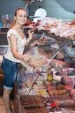 Mujer joven que mira productos de carne Imagenes de archivo