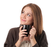 Mujer joven que mira que detiene una taza Fotos de archivo