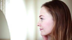 Mujer joven que mira se en espejo almacen de video