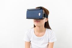 Mujer joven que mira sin embargo el dispositivo de VR Fotografía de archivo libre de regalías