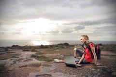 Mujer joven que mira su ordenador portátil Imagenes de archivo