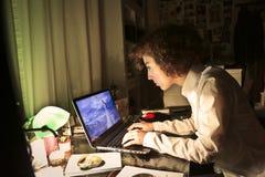 Mujer joven que mira su ordenador portátil Foto de archivo