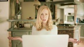 Mujer joven que mira su ordenador portátil chocado por lo que ella ve almacen de video