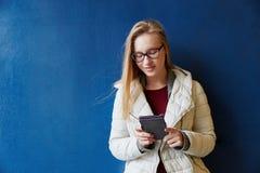 Mujer joven que mira su smartphone Imagenes de archivo