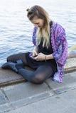 Mujer joven que mira su teléfono Imagenes de archivo