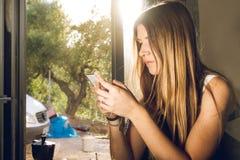 Mujer joven que mira su teléfono celular en casa y que bebe el café foto de archivo libre de regalías