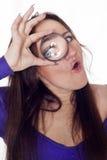 Mujer joven que mira a través de la lupa Imagenes de archivo