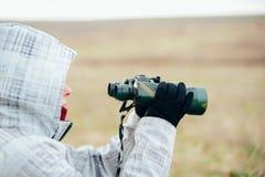 Mujer joven que mira a través de los prismáticos en una naturaleza del otoño Binoc Imagenes de archivo