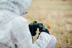 Mujer joven que mira a través de los prismáticos en una naturaleza del otoño Binoc Imágenes de archivo libres de regalías