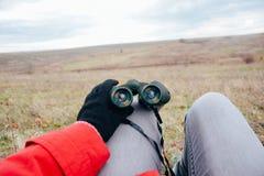 Mujer joven que mira a través de los prismáticos en una naturaleza del otoño Binoc Fotos de archivo libres de regalías