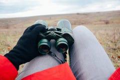 Mujer joven que mira a través de los prismáticos en una naturaleza del otoño Binoc Fotografía de archivo