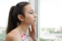 Mujer joven que mira a través de una ventana Fotos de archivo