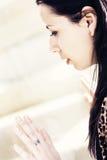 Mujer joven que mira a través de ventana Imagen de archivo libre de regalías