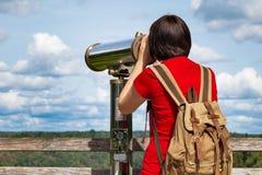 Mujer joven que mira a través del telescopio turístico Fotografía de archivo