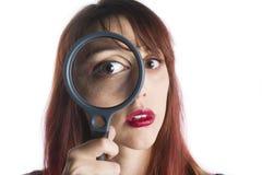 Mujer joven que mira a través de la lupa Foto de archivo