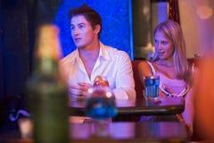 Mujer joven que mira a un hombre joven en un club nocturno Imagen de archivo