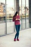Mujer joven que mira un smartphone Fotos de archivo libres de regalías