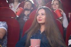 Mujer joven que mira una película en el cine Foto de archivo libre de regalías