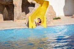 Mujer joven que monta abajo de un diapositiva-hombre del agua que disfruta de un paseo del tubo del agua Imagen de archivo libre de regalías
