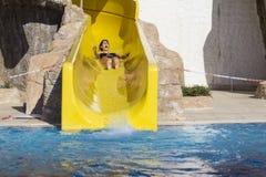 Mujer joven que monta abajo de un diapositiva-hombre del agua que disfruta de un paseo del tubo del agua Fotografía de archivo libre de regalías