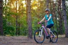 Mujer joven que monta la bici en el rastro en el pino de hadas hermoso Forest Adventure y el concepto del viaje Fotografía de archivo
