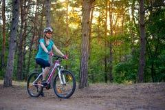 Mujer joven que monta la bici en el rastro en el pino de hadas hermoso Forest Adventure y el concepto del viaje Fotografía de archivo libre de regalías