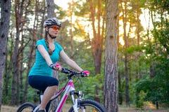 Mujer joven que monta la bici en el rastro en el pino de hadas hermoso Forest Adventure y el concepto del viaje Foto de archivo