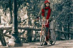 Mujer joven que monta la bici roja del vintage el temporada de otoño Imagen de archivo libre de regalías