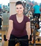 Mujer joven que monta las bicicletas inmóviles Imagen de archivo