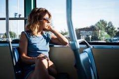 Mujer joven que monta un autobús público foto de archivo