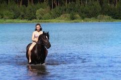 Mujer joven que monta un caballo en el agua Fotos de archivo libres de regalías