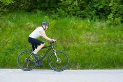 Mujer joven que monta una bici en el camino a través de bosque Imagen de archivo libre de regalías