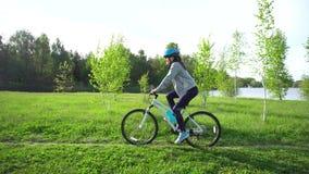 Mujer joven que monta una bici a través del parque en el fondo de un lago o de un río almacen de metraje de vídeo