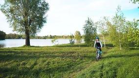 Mujer joven que monta una bici a trav?s del parque en el fondo de un lago o de un r?o metrajes